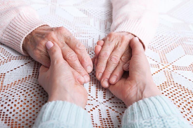 De zorg is thuis van bejaarden Hogere vrouw met hun verzorger thuis Concept gezondheidszorg voor bejaarde oude mensen stock afbeelding