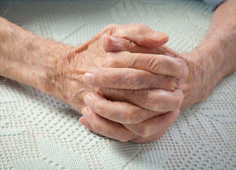 De zorg is thuis van bejaarden. Oude mensen die handen houden. stock afbeeldingen
