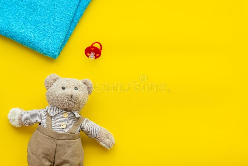 De zorg van de baby Pasgeboren babyconcept Teddybeerstuk speelgoed dichtbij fopspeen op gele achtergrond hoogste meningsruimte vo royalty-vrije stock foto