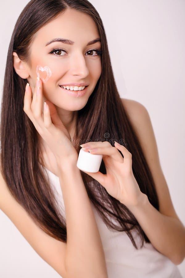 De zorg van de conceptenhuid Een jonge gezonde vrouw met kosmetische room  stock foto