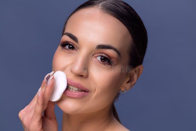 De Zorg van de schoonheidshuid Mooie gelukkige vrouw die usi van de gezichtsmake-up verwijderen stock foto's