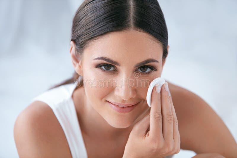 De zorg van de gezichtshuid Mooie Vrouw die Make-up met Katoenen Stootkussen verwijderen stock fotografie