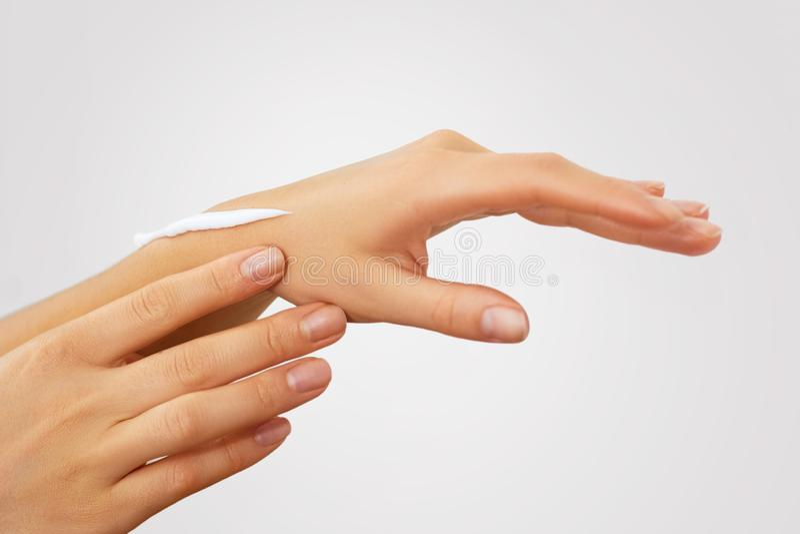 De Zorg van de handhuid Sluit omhoog van vrouwelijke handen toepassend room, lotion Mooie vrouwenhanden met rode manicure stock fotografie
