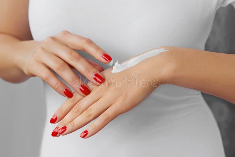 De Zorg van de handhuid Sluit omhoog van vrouwelijke handen toepassend room, lotion Mooie vrouwenhanden met rode manicure Spijker royalty-vrije stock afbeeldingen