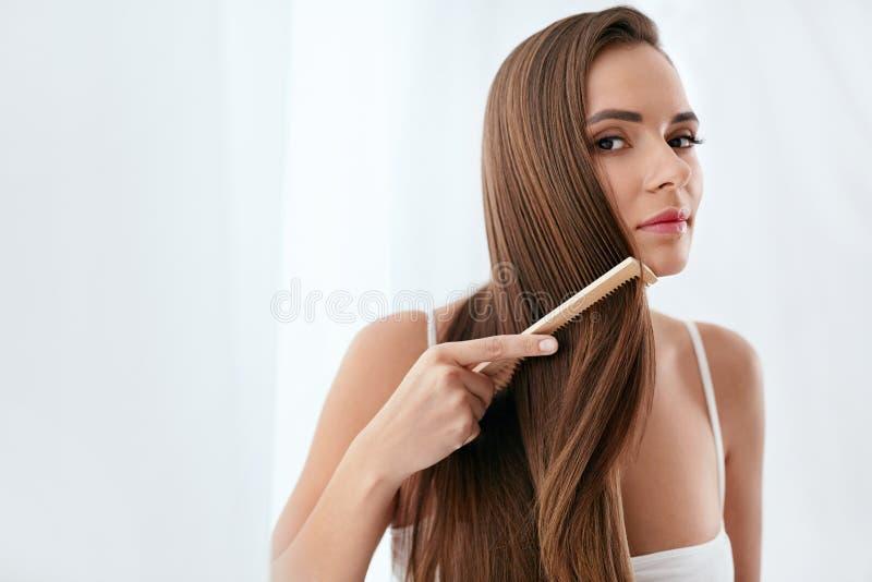 De zorg van het haar Vrouw die Mooi Lang Haar met Houten Borstel kammen stock fotografie
