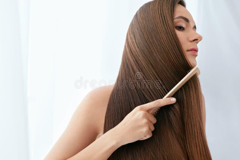 De zorg van het haar Vrouw die Mooi Lang Haar met Houten Borstel kammen stock foto's