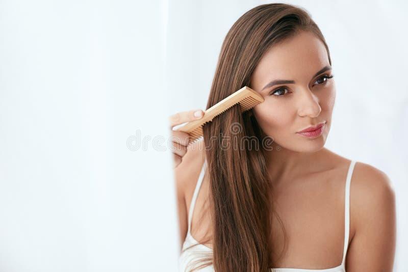 De zorg van het haar Vrouw die Mooi Lang Haar met Houten Borstel kammen royalty-vrije stock foto's