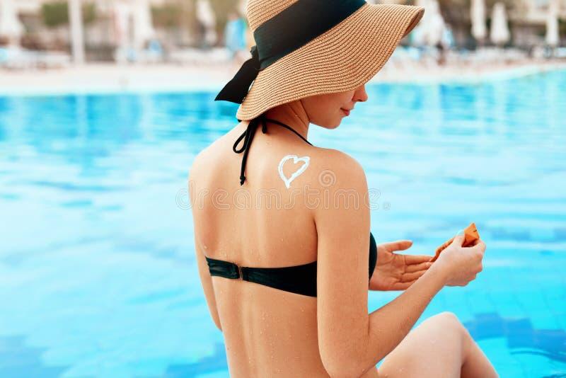 De zorg van de huid Vrouw die zonneroom op schouder zetten dichtbij de pool Het meisje past zonroom toe Vrouw met Zonnebrandolie  royalty-vrije stock afbeelding