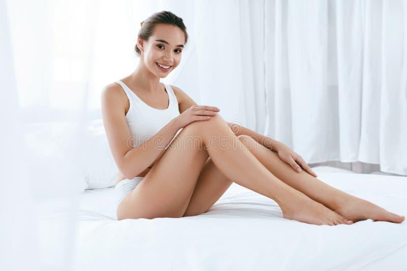 De zorg van de lichaamshuid Mooie Vrouw wat betreft Lange Benen op Wit Bed royalty-vrije stock foto