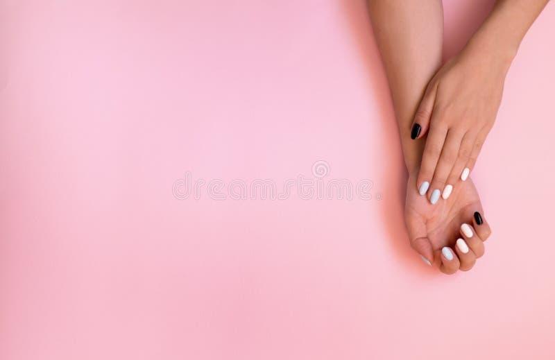 De zorg van meisjesspijkers Modieuze in vrouwelijke manicure Mooie jonge vrouwen` s handen op roze achtergrond stock afbeeldingen