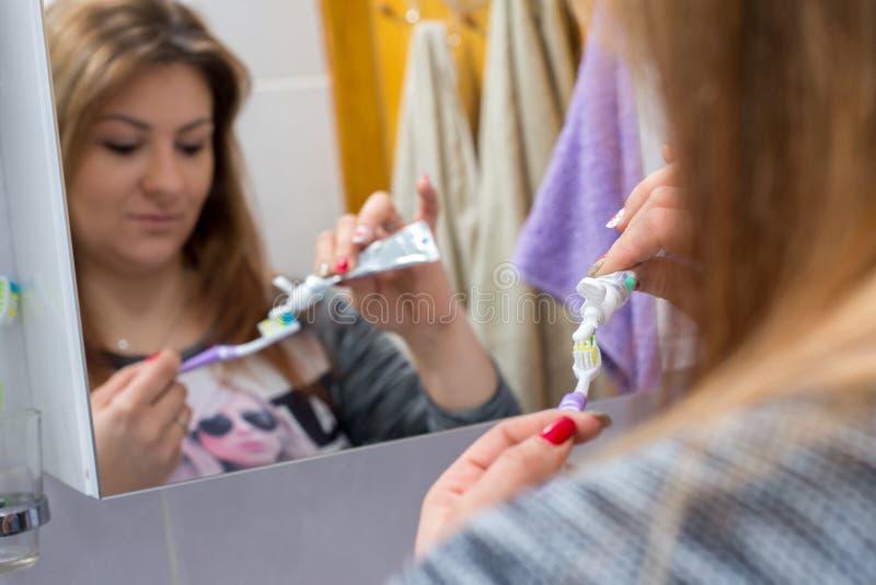 De zorg van ochtendtanden, jonge vrouw in badkamers stock afbeeldingen