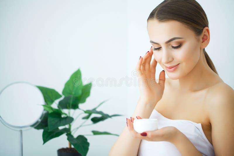De Zorg van de schoonheidshuid Mooie Vrouw die Kosmetische Gezichtsroom toepassen stock afbeelding