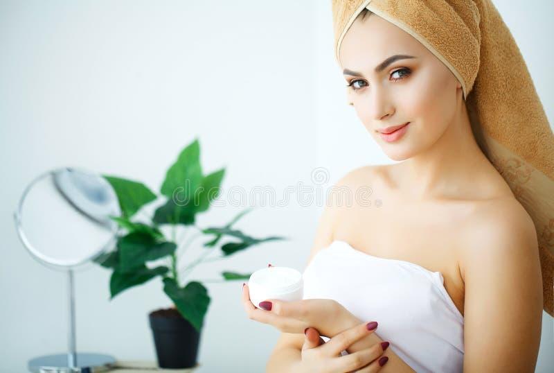 De Zorg van de schoonheidshuid Mooie Vrouw die Kosmetische Gezichtsroom toepassen royalty-vrije stock afbeelding