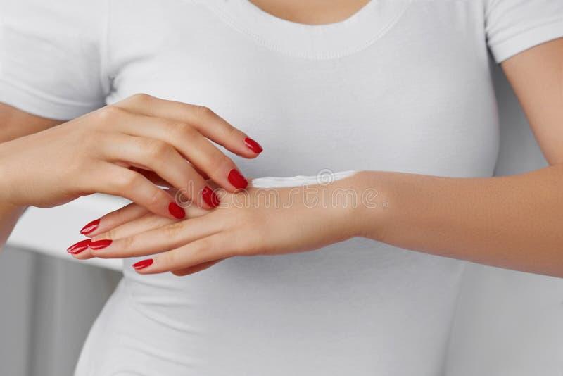 De zorgconcept van de huid Mooie Vrouw met Handroom, Lotion op Haar Handen Sluit omhoog Foto van Vrouwelijke Handen met het Rode  stock fotografie