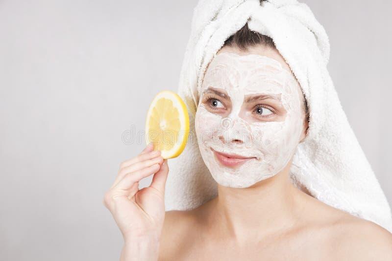 De zorgconcept van de schoonheidshuid De aantrekkelijke Kaukasische vrouw met gezichtsmasker op gezicht houdt citrusvruchten op h royalty-vrije stock foto