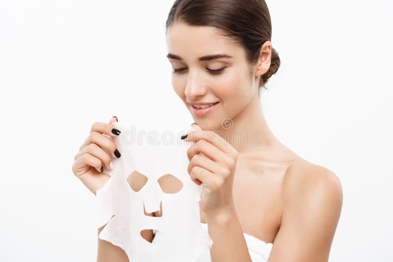 De Zorgconcept van de schoonheidshuid - Mooie Kaukasische Vrouw die document bladmasker op haar toepassen gezichts witte achtergr royalty-vrije stock afbeeldingen