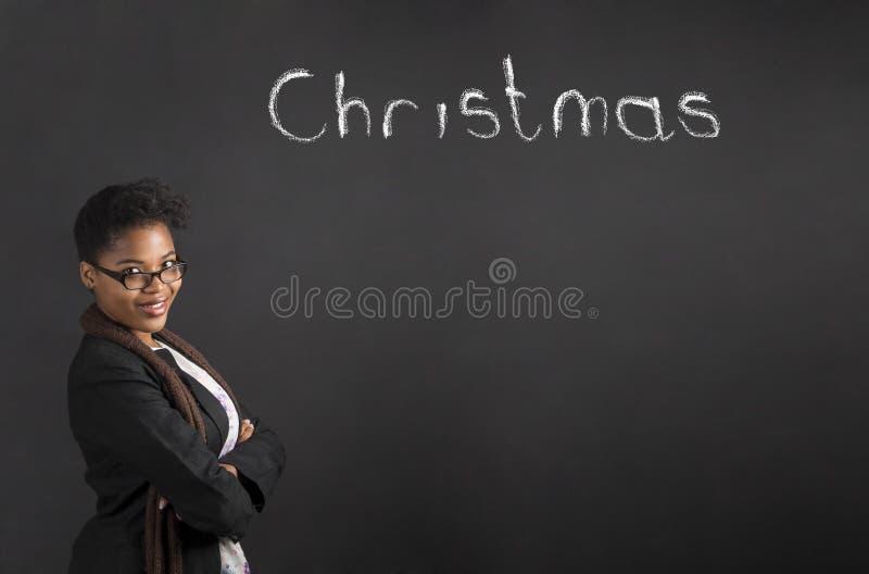 De Zuidafrikaanse of Afrikaanse Amerikaanse vrouwenleraar of de student met wapens vouwde het denken over Kerstmis op backgrou va royalty-vrije stock afbeelding