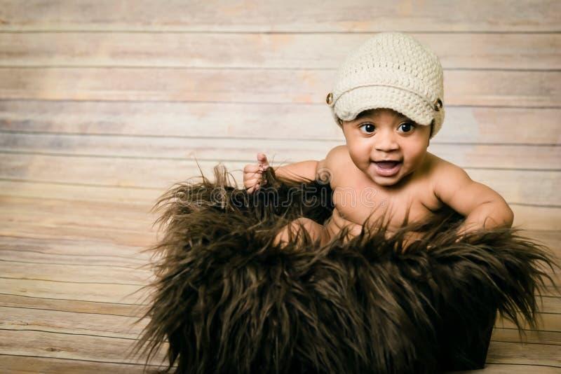De zuigeling mengde ras het gezonde kijken babyjongen die gebreide hoedenzitting in een pluizige bontmand houten moderne sh studi royalty-vrije stock fotografie