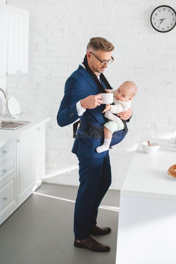 de zuigelingsdochter van de zakenmanholding in babydrager en kop met drank stock afbeelding