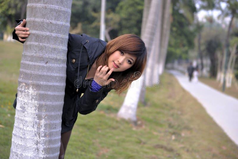 De zuivere Mooie Aziatische tribune van het Meisje door een boom stock afbeelding