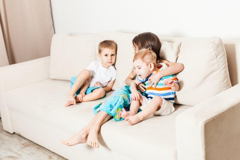 De zuster en twee jongere broers zitten op een witte bank stock afbeeldingen