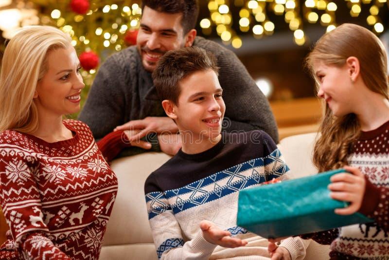 De zuster geeft gift aan broer op Kerstmisvooravond royalty-vrije stock afbeelding