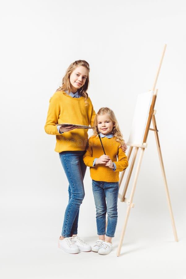 de zusters van verschillende generaties met palet en verf borstelen status voor schildersezel royalty-vrije stock foto