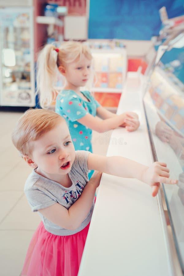 De zustersvrienden die van meisjeskinderen het venster van de roomijswinkel bekijken royalty-vrije stock fotografie
