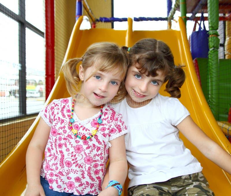 De zustervrienden van meisjes op speelplaats stock afbeeldingen