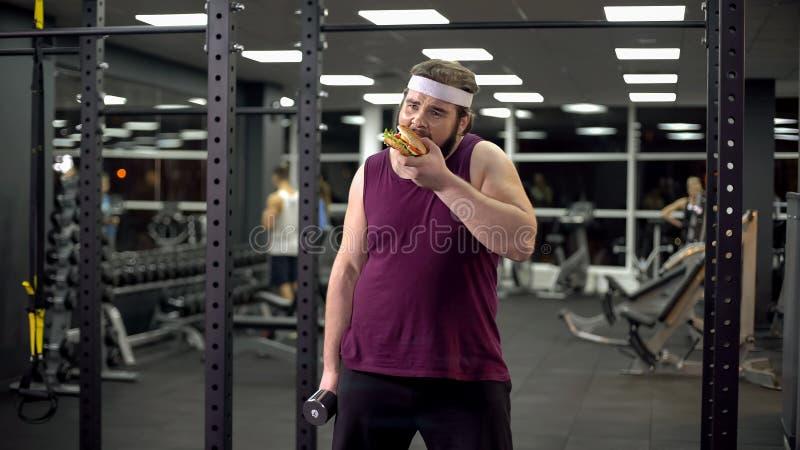 De zwaarlijvige domoor die van de mensenholding hamburger eten, die van het doen van sport, verslaving weigeren royalty-vrije stock fotografie
