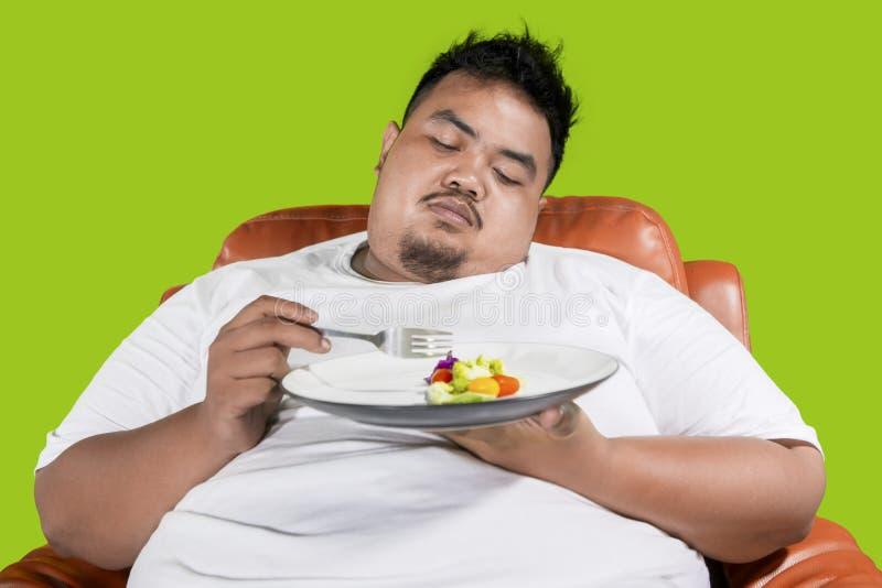 De zwaarlijvige mens kijkt lui om voedsel op studio te eten royalty-vrije stock fotografie
