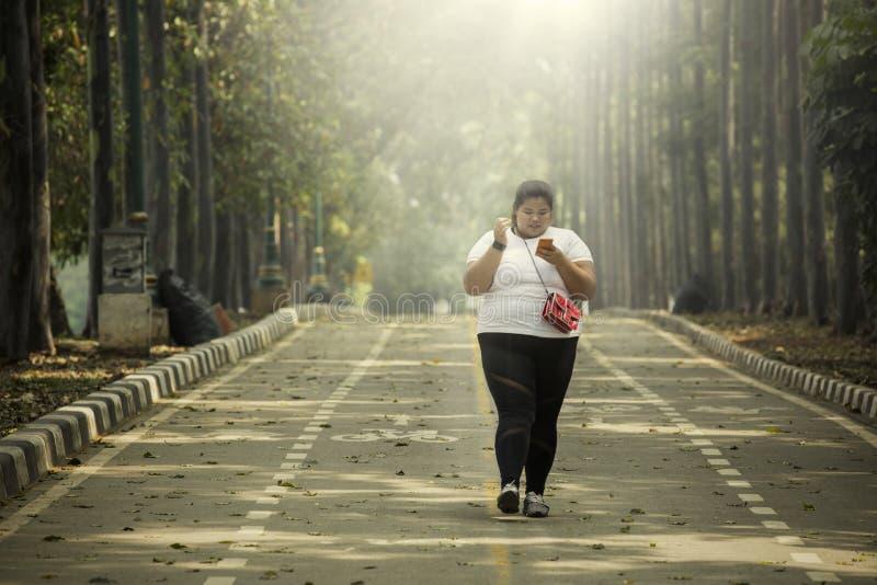 De zwaarlijvige vrouw gebruikt een telefoon op de weg stock afbeelding