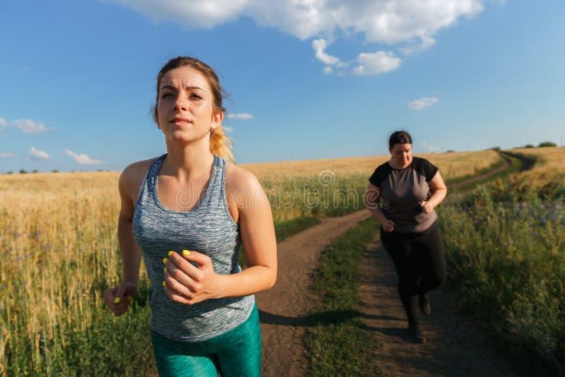 De zwaarlijvige vrouw heeft korte adem bij openluchtjogging stock foto