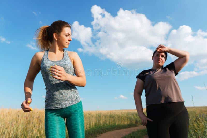 De zwaarlijvige vrouw heeft korte adem bij openluchtjogging stock afbeelding