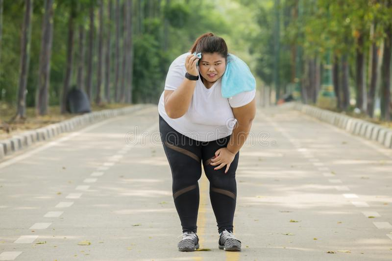 De zwaarlijvige vrouw kijkt vermoeid na het lopen stock foto