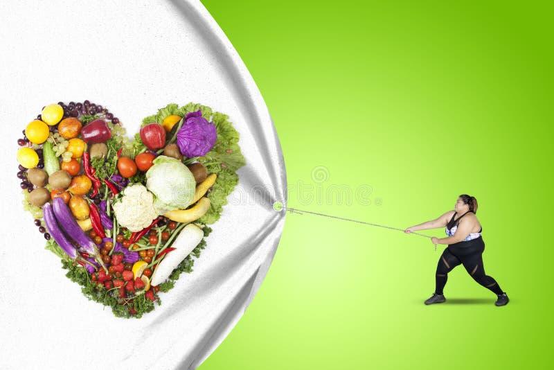 De zwaarlijvige vrouw trekt organisch voedsel vormde een hart stock foto's