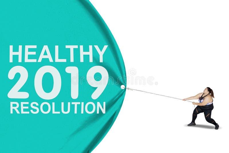 De zwaarlijvige vrouw trekt tekst van gezonde resolutie voor 2019 stock foto