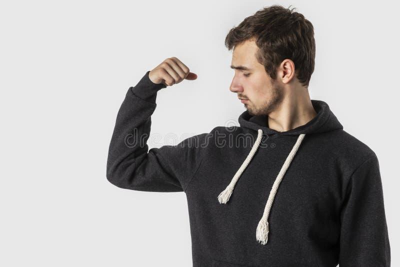 De zwakke Kaukasische jonge mens bekijkt disappointedly zijn bicepsen Geïsoleerdj op witte achtergrond Zwakheidsconcept stock fotografie