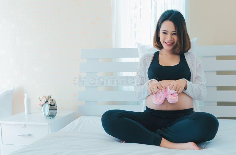 De zwangere Aziatische vrouwen hebben pret met babyschoenen Zij is gelukkig met de wachttijd voor haar baby stock afbeelding
