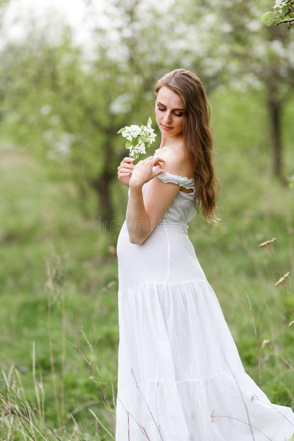 De zwangere bruid in de tuin Witte het huwelijkskleding van de bohostijl Groene bomen en zon Mooi zwanger meisje in een witte kle stock foto