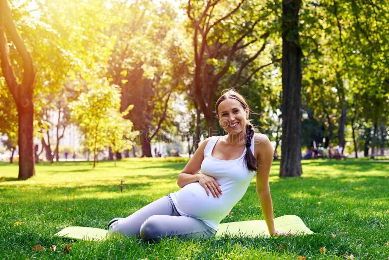De zwangere hand van de vrouwenholding op buik tijdens yogatraining in park royalty-vrije stock foto