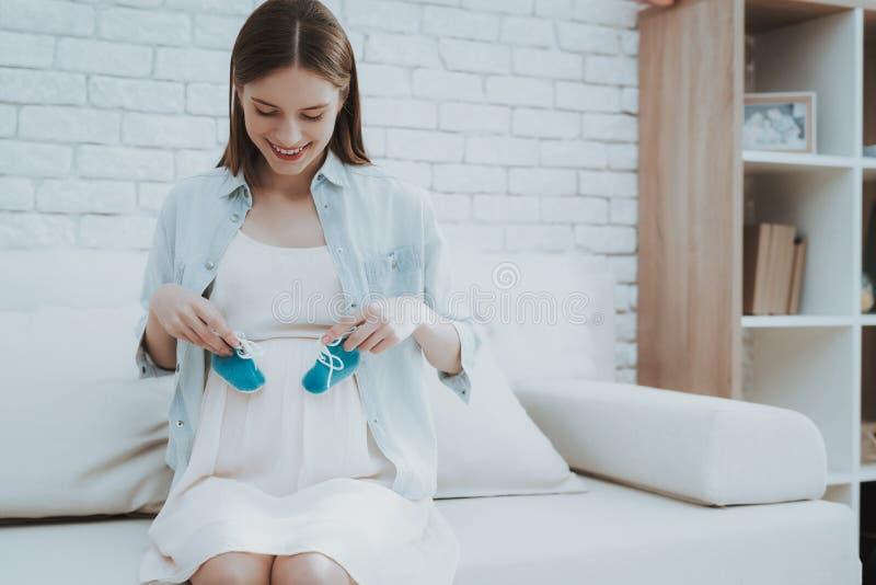 De zwangere Jonge Vrouw houdt Schoenen voor Pasgeboren stock foto