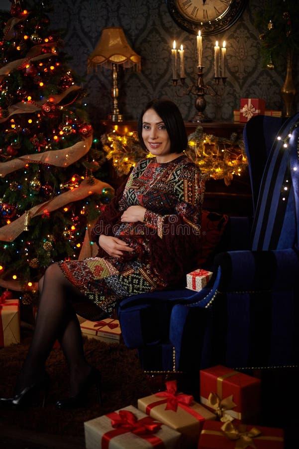 De zwangere meisjeszitting met stelt bij een Kerstboom voor stock foto's