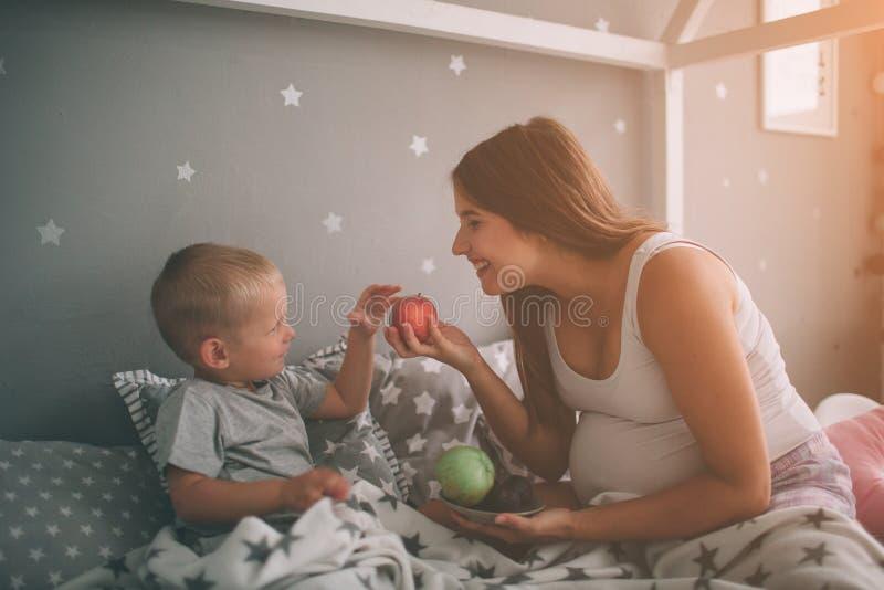 De zwangere moeder en weinig jongenszoon eten een appel en een perzik in het bedt huis in de ochtend Toevallige levensstijl binne royalty-vrije stock fotografie