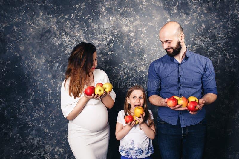 De zwangere moeder, de gebaarde vader, en weinig dochter houden appelen in hun handen en willen hen eten royalty-vrije stock afbeelding