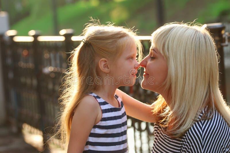 De zwangere mooie moeder en haar weinig dochter stellen in sunn royalty-vrije stock foto