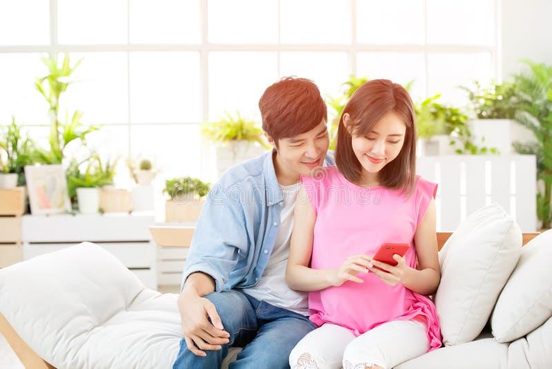 De zwangere smartphone van het paargebruik royalty-vrije stock afbeelding