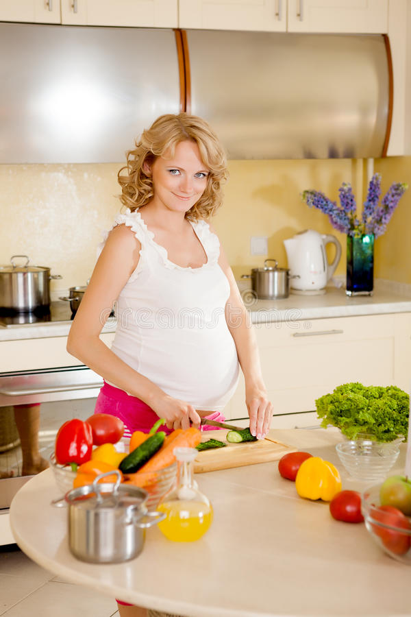 De zwangere vrouw bereidt plantaardige salade voor stock afbeeldingen