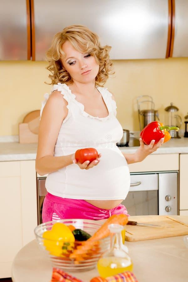 De zwangere vrouw bereidt plantaardige salade voor royalty-vrije stock foto's
