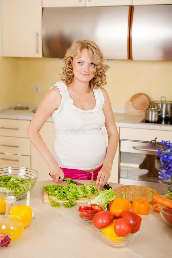 De zwangere vrouw bereidt plantaardige salade voor royalty-vrije stock foto